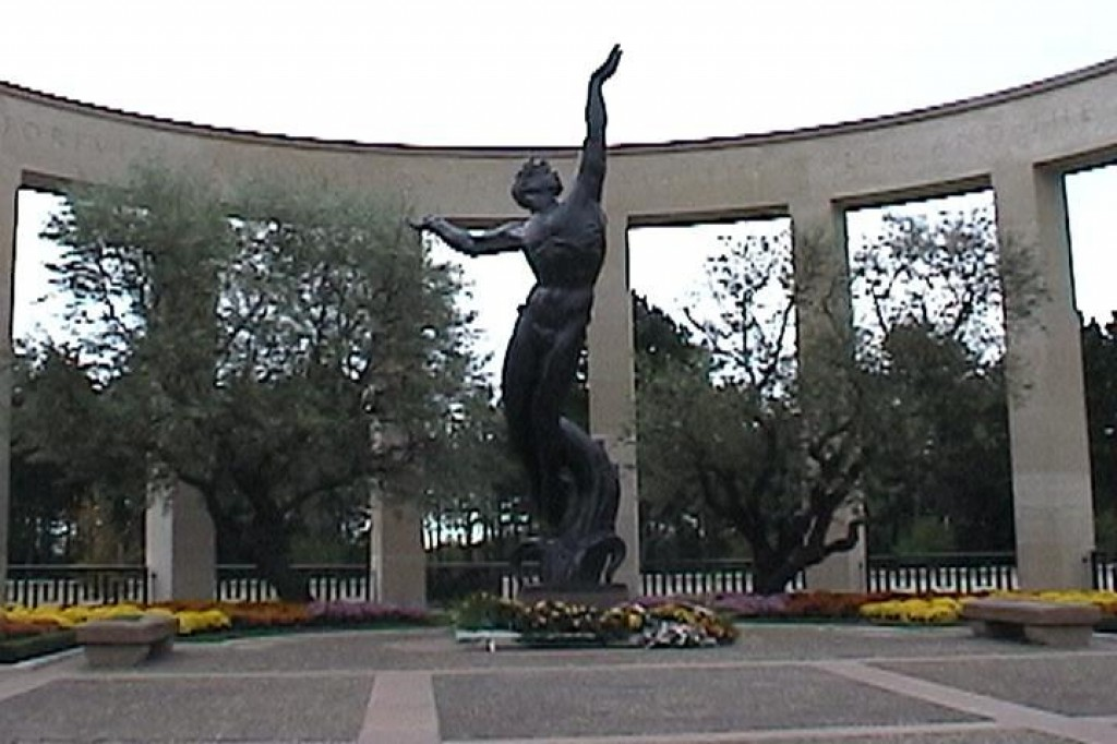 "At one end of the cemetery stands this memorial.  The statue is called the ""American Youth Rising from the Waves"".  The inscription around the top of the memorial reads, ""This embattled shore portal of freedom is forever hallowed by the ideals the valor and the sacrifices of our fellow countrymen."""
