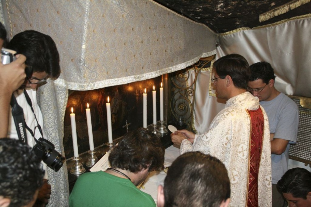Armenian Priest leading a prayer group in the Grotto of the Nativity