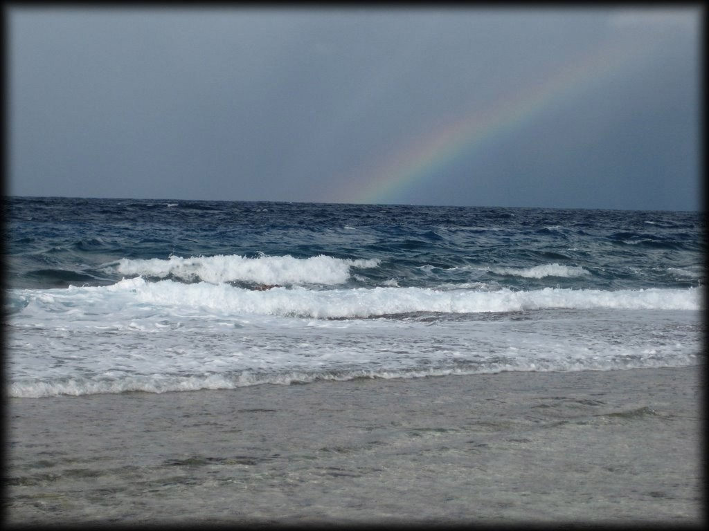 A rainbow in the distance over the ocean.