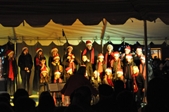 Carolers perform on stage at the 2nd Annual Charlie Brown Christmas Tree Grove on Windsor Town Green.